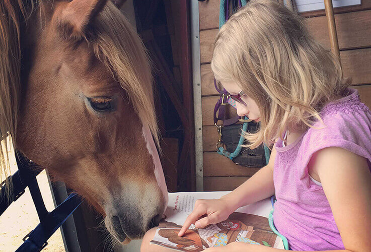 Young girl reading book to a horse