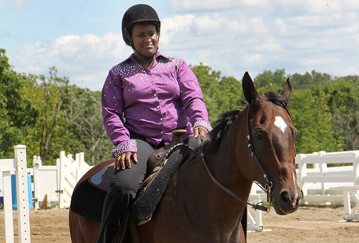 Young woman in purple shirt on horseback