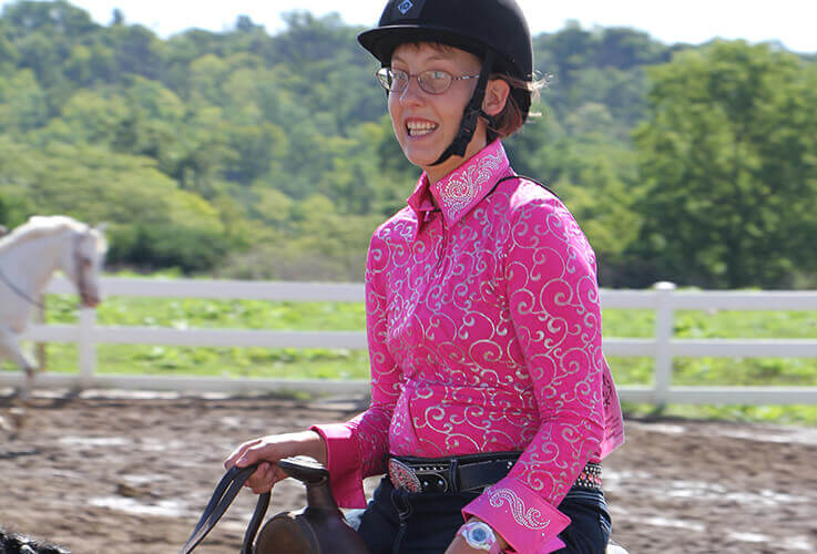 Young woman with pink shirt on horseback