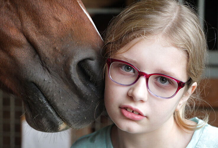 Young girl in glasses nudged by horse