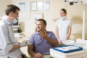 Smiling man talking to dentist