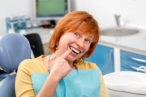 Senior woman in dental chair pointing to healthy smile