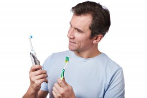 man comparing manual and electric toothbrush