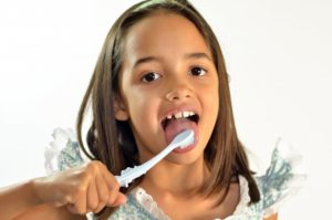 A young girl brushing her teeth.