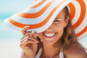 woman in sun hat with dental implants in Gahanna smiles