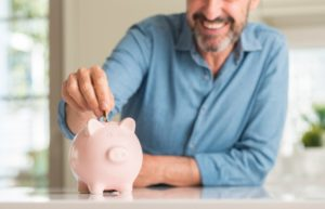 man putting coins into a pink piggy bank